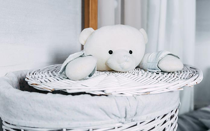 Hamper and stuffed bear in pale blue bedroom of child with autism