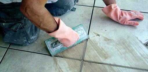 Applying grout to joints in tile