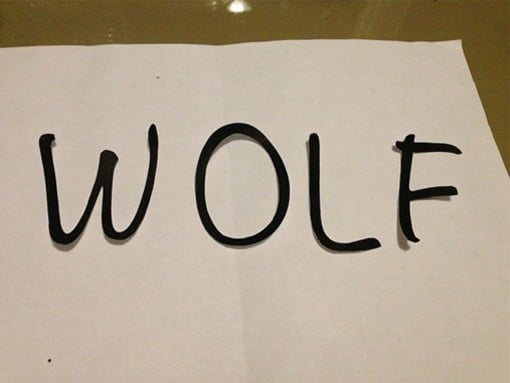 Black wolf letters cut out of paper