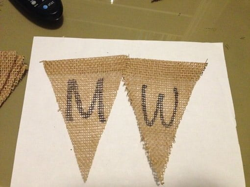 Letter M traced on burlap triangle with permanent marker next to letter W