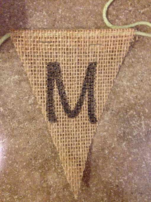 Burlap triangle with letter M on green yarn