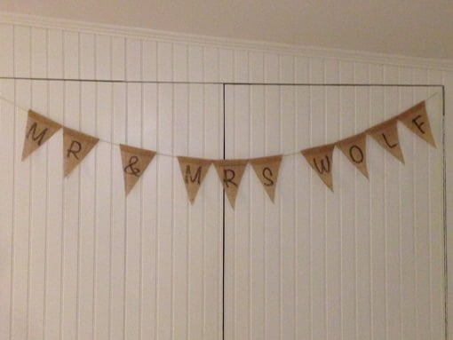 Burlap bunting hanging over white beaded board wall