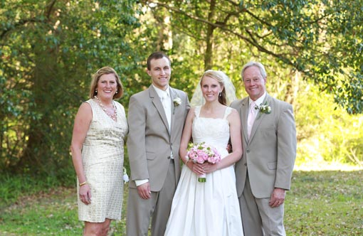 Bride and groom posing with bride's parents on sunny day.