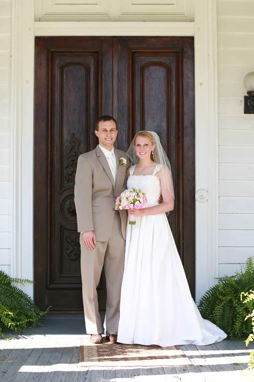 Bride and groom in tan suit posing in front of wooden door