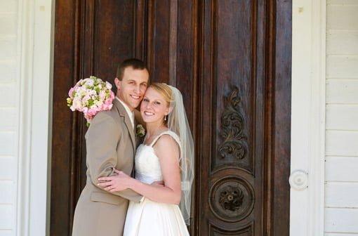 Bride and groom posing in front of big wooden door.