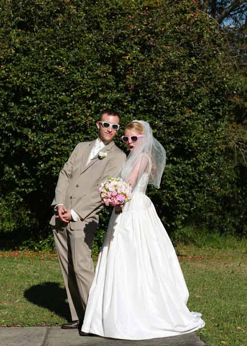 Bride and groom posing silly with sunglasses