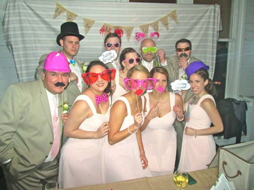 Bridal party posing in photo booth with props and burlap bunting banner