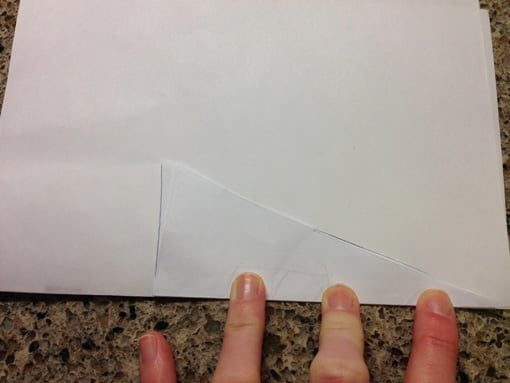 Triangle folded in half and placed on edge of folded computer paper