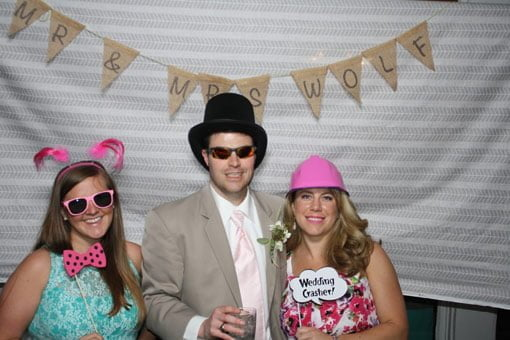 Wedding photo booth with fabric background, pink sunglasses, pink construction hat and 2 girls.