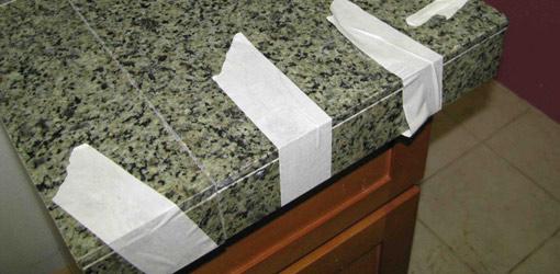Applying granite tile to a countertop edge.