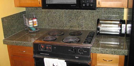 Finished granite tile countertop around stove.