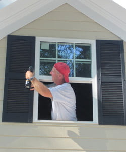 Installing shutters on a house.