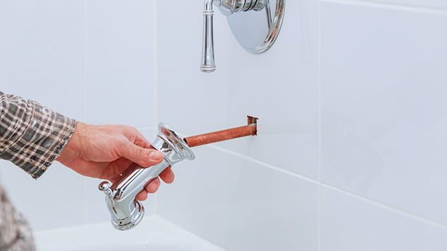 Plumber working in faucet with thermostat