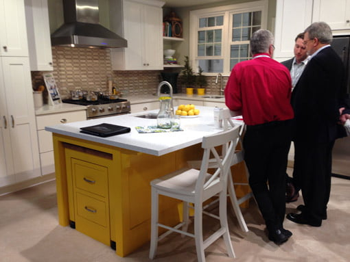 Yellow kitchen cabinet island with white countertop.