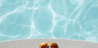 A pair of sunglasses sitting on the edge of a gunite pool