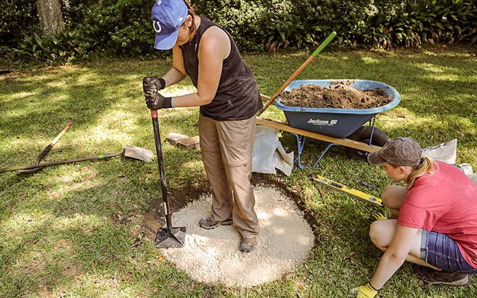 Audra tamps down paver base while Chelsea Lipford Wolf looks on