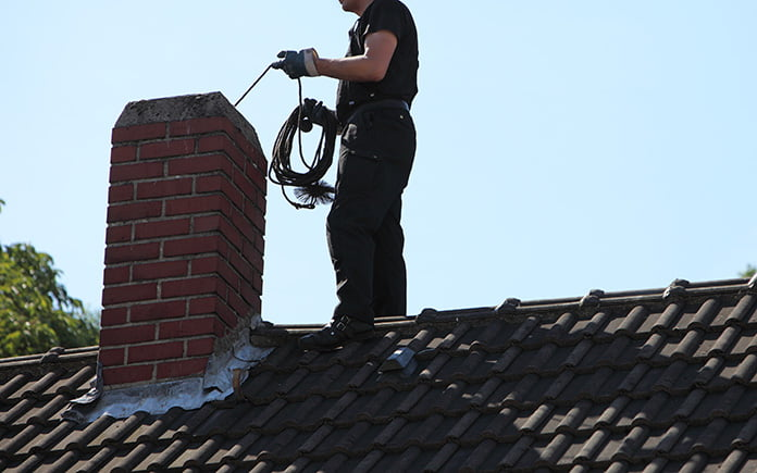 Chimney sweep, on a roof, cleaning a chimney with a brush tool
