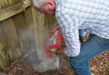 Danny Lipford pouring concrete mix into a fence hole