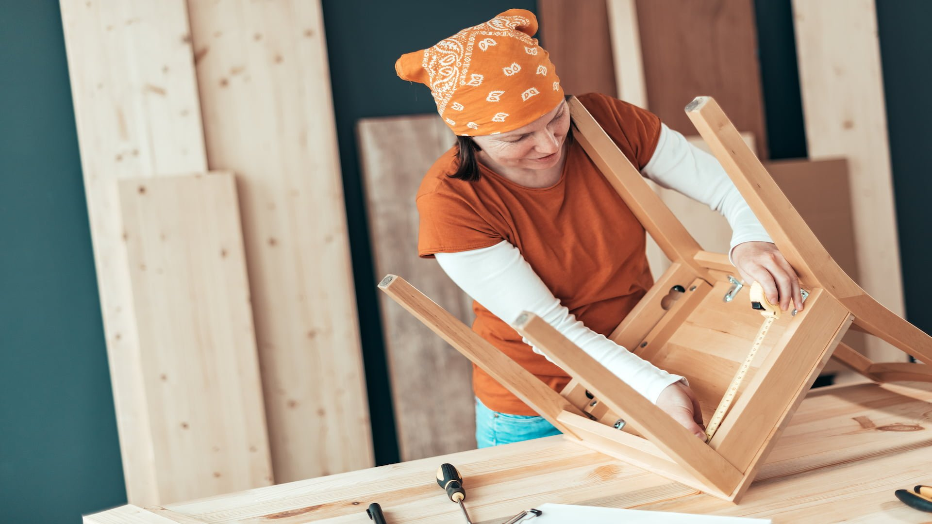Female carpenter repairing wooden chair legs in small business woodwork workshop
