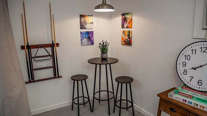 Bistro set in a corner of the room with wall art hanging on adjoining walls and a rack for pool sticks