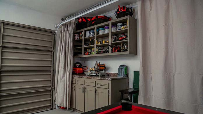 Nook for father's tools includes cabinets and shelves hidden with a drop cloth curtain