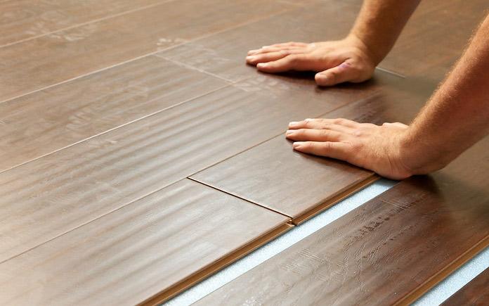 A man installing laminate plank flooring