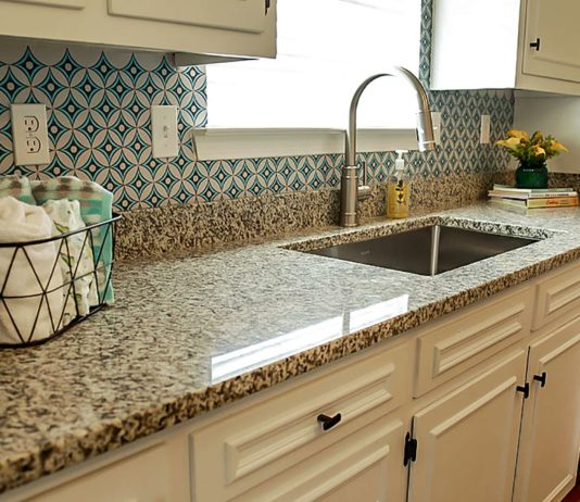 Granite countertops in a kitchen with a window overlooking the sink