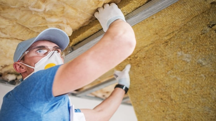 Man installing insulation in an attic