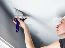 Woman Painting Popcorn Ceiling During Home Remodeling