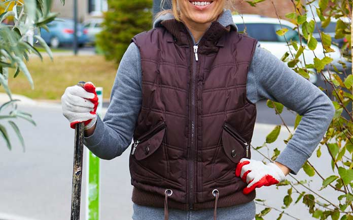 Woman standing with a rake wearing comfortable gloves for the chore