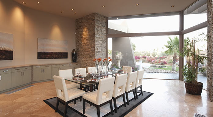 Recessed lights over a dining room table with wall-size window letting in natural light