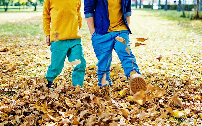 Two boys stomp on leaves in the fall after their mother has taken a phone break