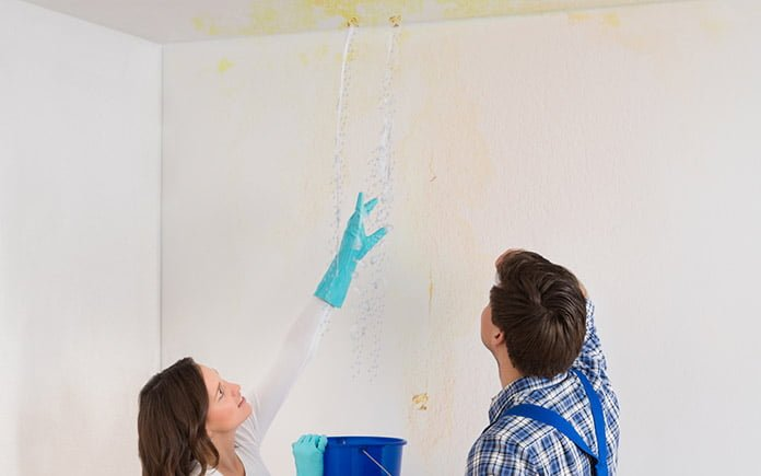 Woman pointing out water stains to man