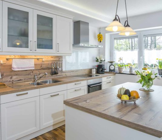 Kitchen with ambient lighting including pendant lights, natural light and under cabinet lighting