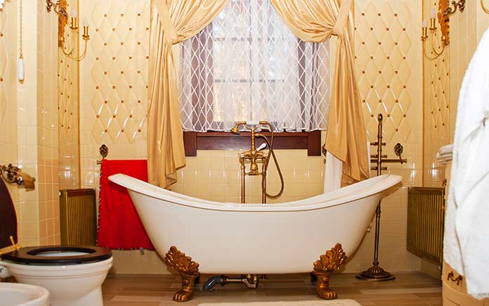Antique clawfoot bathtub in bathroom with yellow wallpaper and gold curtains