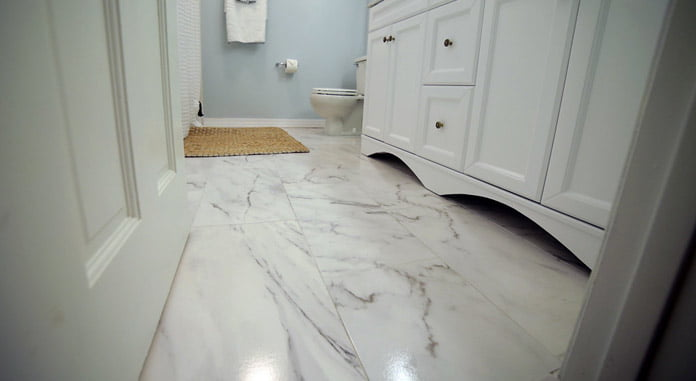 White bathroom with ceramic tile that looks like marble