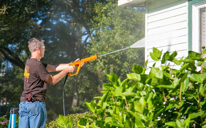 A man pressure washing the vinyl siding on a home
