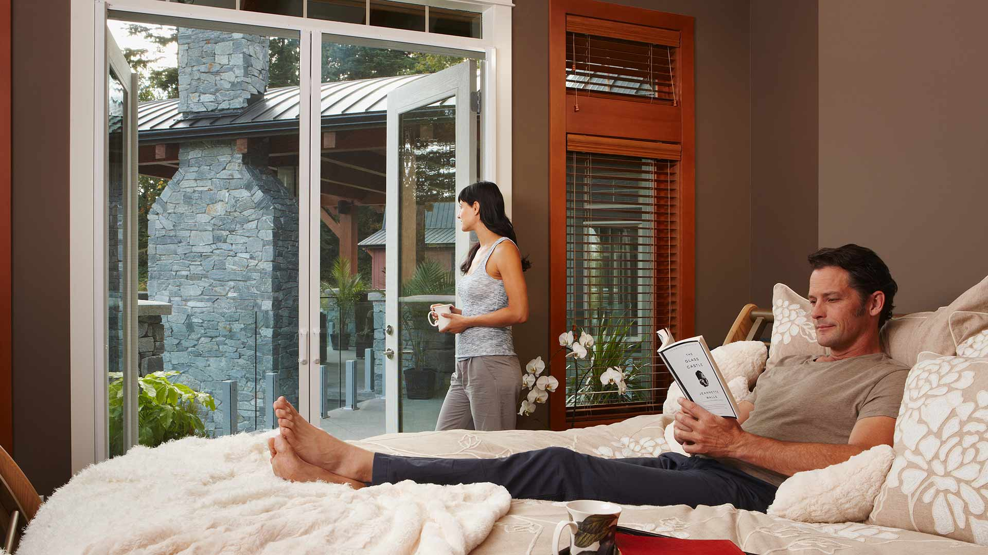 Woman looking outside through Phantom Screens while man waits for her in bed