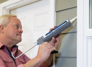 Danny Lipford caulks around the windows outside a home.