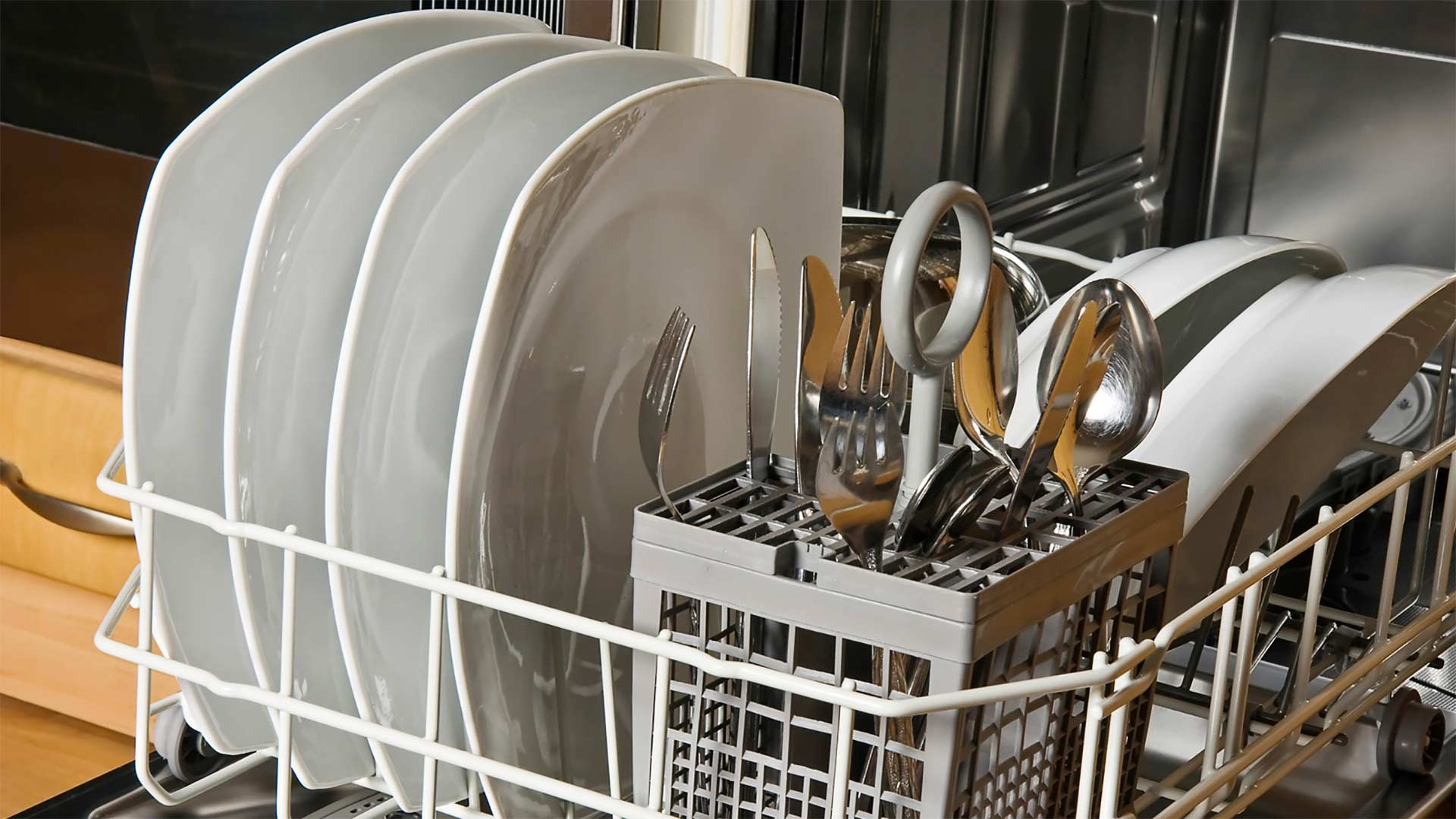 Dishes and flatware waiting to be washed in a dishwasher