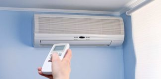 Person aiming remote control toward ductless mini-split air conditioner installed on a wall just below the ceiling.