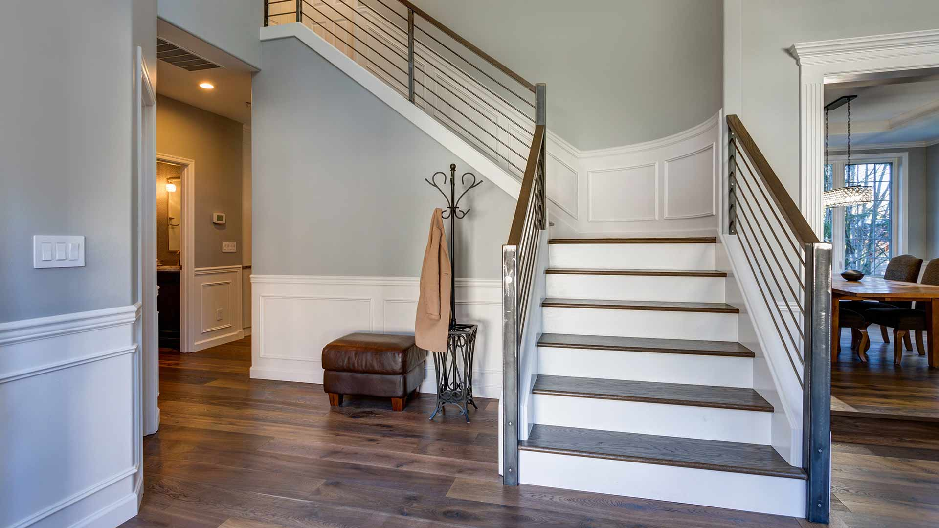 Foyer with stairs leading to the second floor, wainscoting and ambient lighting