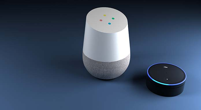 Digital assistants Google Home and Amazon Echo, sitting side by side