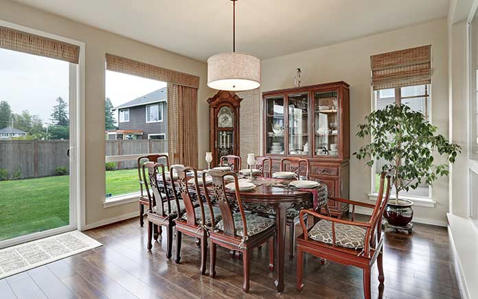 Formal dining room with expansive view of backyard and grandfather clock in the corner.
