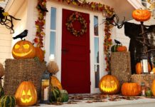 Front porch of a home during the morning, with jack-o-lanterns on the floor and fall decorations adorning the wood trim