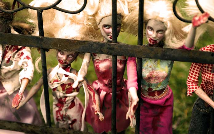 Plastic dolls made up to appear bloody and disheveled, imprisoned behind a metal fence