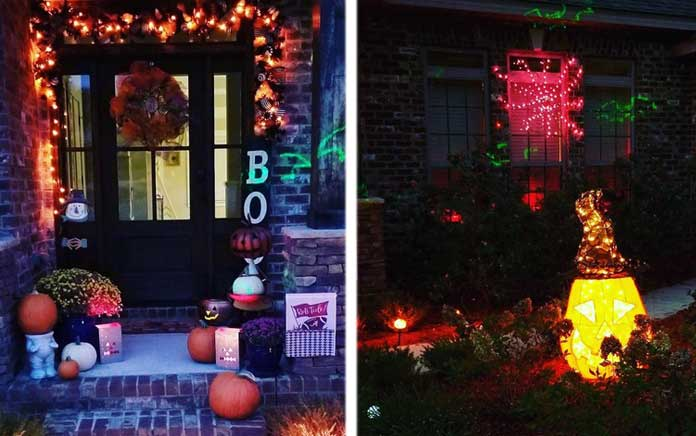 A brick home adorned with Halloween decorations (orange string lights, a Boo sign, and various lawn fixtures)