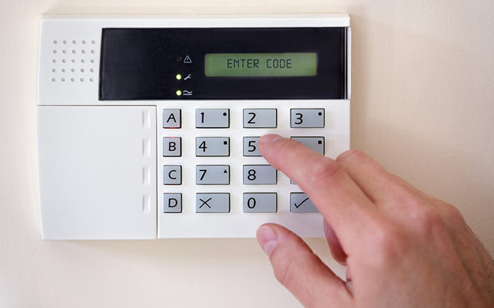 Finger pressing a key on a wireless home security system's keypad