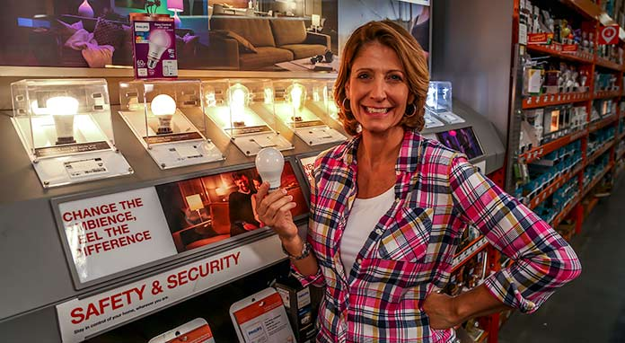 Jodi Marks holding a Philips Wi-Fi Light Bulb at The Home Depot