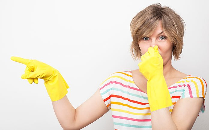Woman wearing rubber gloves, holding her nose and pointing to a smelly dishwasher